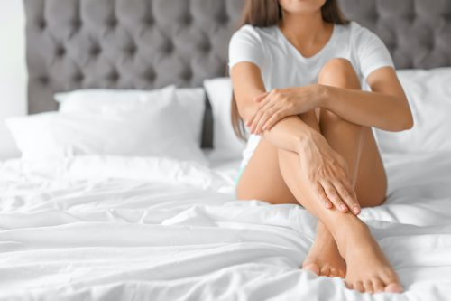 jonge vrouw met mooie benen op een bed