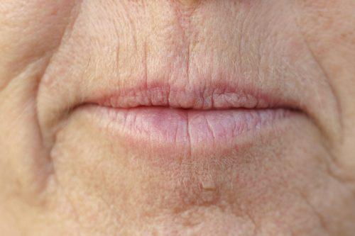 close up van de mond van een vrouw van middelbare leeftijd met rimpels rondom de mond