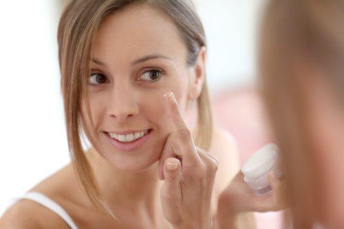 meisje brengt gezichtscreme aan op de huid, lachend en staande voor de spiegel.