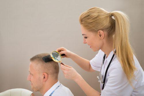 haartransplantatiespecialist Nationaal Huidcentrum beoordeelt het haar van een cliënt