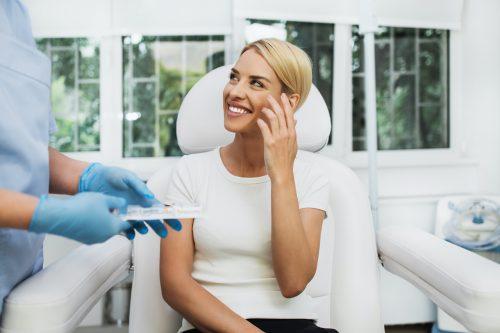 Knappe en blije vrouw in een cosmetische kliniek die lachend met de cosmetisch arts aan het praten is.