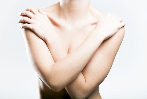 Vrouw die borsten met haar armen beschermt